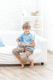 看电视的年轻男孩室内画象 库存照片