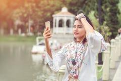 看电话的亚裔妇女照片 免版税库存照片