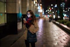 看电话的少妇在晚上 免版税库存图片