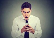 看电话的惊奇的人看见意外消息或照片激动奇迹在面孔 免版税库存图片