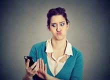 看电话的震惊急切害怕的女孩看见坏消息照片 免版税库存图片