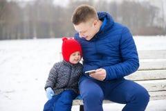 看电话` s屏幕的父亲和女儿 免版税图库摄影