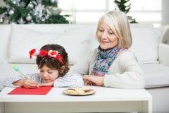 看男孩文字信件的祖母对圣诞老人 库存照片