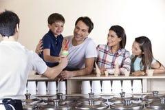 看男孩的家庭,当服务他冰淇凌时的侍者 免版税图库摄影