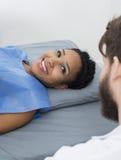 看男性医生While Lying On Bed的妇女 免版税图库摄影