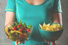 看的健康年轻女人健康和不健康的食物,设法做出正确的选择 免版税库存照片