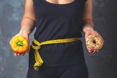 看的健康年轻女人健康和不健康的食物,设法做出正确的选择 图库摄影
