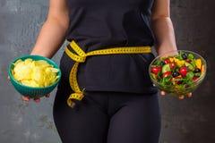 看的健康年轻女人健康和不健康的食物,设法做出正确的选择 库存照片