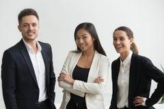 看的千福年的微笑的不同种族的办公室专家 免版税库存照片