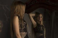 看的可爱的妇女在镜子的反射 免版税库存图片