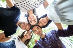 看的圈子的年轻愉快的朋友拥抱和下来 免版税库存图片