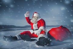 看的圣诞老人坐在与膝上型计算机的雪和  免版税库存照片