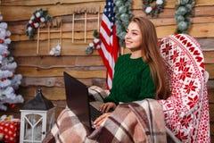 看的女孩与膝上型计算机坐椅子和直接 免版税库存照片