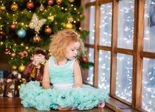 看的女孩坐在圣诞树附近和  库存图片
