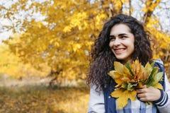 看的女孩拿着手中束叶子和斜向一边 库存照片
