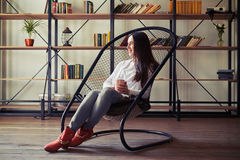 看的妇女坐在设计师椅子和  免版税库存照片