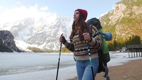 看的年轻女人步行在与一个大背包的lago di braies海岸和  股票视频