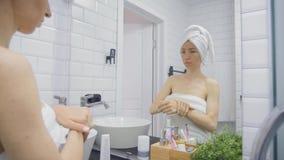 看的毛巾的年轻女人应用奶油面对和在家反映卫生间 秀丽,生活方式,皮肤护理概念 股票视频