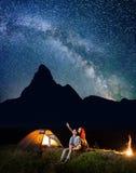 看的浪漫夫妇远足者在晚上发光满天星斗的天空 坐在阵营和营火附近的愉快的对 库存图片