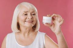 看皮肤举的奶油的宜人的迷人的妇女 库存图片