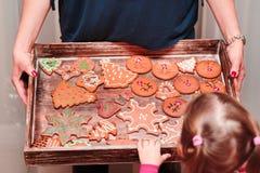 看盘子的小女孩用圣诞节曲奇饼填装了 库存图片