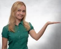 看直接入照相机的偶然绿色衬衣的愉快和微笑的年轻女人用开放手 免版税图库摄影