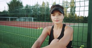 看直接对camere的特写镜头微笑的网球员妇女,她有断裂时光坐地板在 股票视频