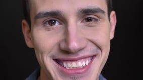 看直接照相机和愉快地微笑与牙的年轻白种人男性特写镜头画象  股票视频