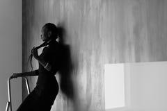 看相当非洲或黑人美国的妇女侧视图接触她在黑暗的演播室背景的厚实的褶,黑和whi 库存照片