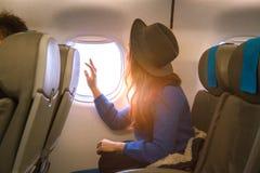 看看法的年轻亚裔妇女旅客在飞机的窗口有幸福和放松的 库存图片