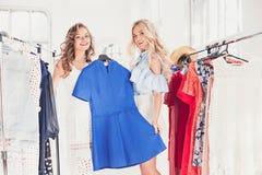 看礼服的两个年轻俏丽的女孩和试穿它,当选择在商店时 库存照片
