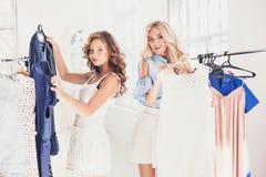 看礼服的两个年轻俏丽的女孩和试穿它,当选择在商店时 免版税库存照片