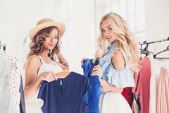 看礼服的两个年轻俏丽的女孩和试穿它,当选择在商店时 免版税库存图片