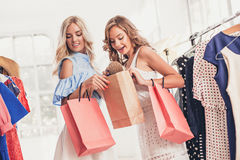 看礼服的两个年轻俏丽的女孩和试穿它,当选择在商店时 免版税图库摄影