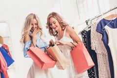 看礼服的两个年轻俏丽的女孩和试穿它,当选择在商店时 图库摄影