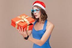 看礼物盒的狡猾女实业家和想要太开放 库存图片