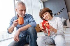 看礼物盒的逗人喜爱的高兴孩子 免版税库存照片