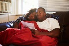 看票据的夫妇在家保留温暖的下面毯子 库存图片