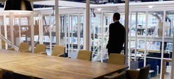 看空的会议室的窗口穿着体面的商人 免版税库存图片