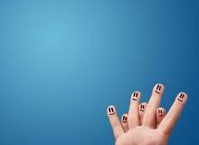 看空的蓝色背景的愉快的兴高采烈的面孔手指复制 免版税图库摄影