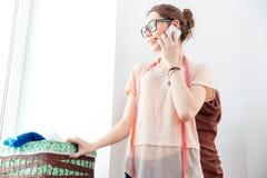 看窗口和使用智能手机的愉快的妇女裁缝 免版税库存照片