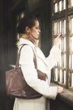 看窗口的一名美丽的妇女的浪漫时尚画象 免版税库存图片