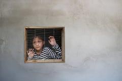 看窗口的亚裔女孩在房子,人交易里被监禁了 免版税库存图片