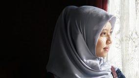 看窗口的亚裔穆斯林 图库摄影