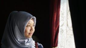 看窗口的亚裔穆斯林 免版税库存图片