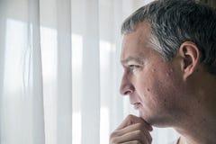 看窗口的哀伤的人 感到绝望 站立在窗口附近的沮丧的成熟人 免版税库存照片