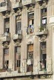 看窗口的妇女被毁坏的阳台洗衣店在哈瓦那,古巴 免版税图库摄影
