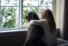 看窗口的小女孩和她的狗。 免版税库存照片