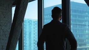看窗口的年轻成功的商人街市 高大厦的商业 顶楼样式的办公室 影视素材