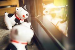 看窗口的愉快的微笑狗玩偶 库存图片